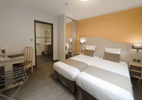 Chambre avec deux lits simples au sein de la résidence thermale.